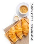 Small photo of Croissants on wooden bread cutting board with sackcloth and with sweetened condensed milk, cappuccino coffee mug, over white background. with clipping path. Croissant french breakfast. Top view.