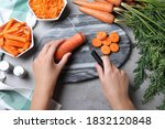 Woman Cutting Carrot At Grey...