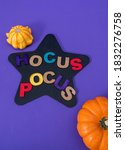 """Small photo of Little pumpkins, """"Hocus Pocus"""", phrase made from wooden letters and black star on purple background"""