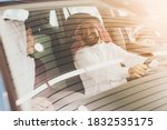 Small photo of A man looks at his wife while holding the wheel in a new car. Arab man sits at the wheel of a new car while his wife sits nearby.