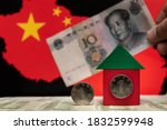 Small photo of Two coins, one yuan each, one of which replaces a window in a stylized notional house against the background of a hand holding a 10 yuan note and the outline of the Chinese border with the flag