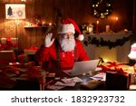 Small photo of Happy Santa Claus waving hand video calling kid talking to child greeting on Merry Christmas, Happy New Year in virtual video online chat on laptop sitting at home table late with present on xmas eve.
