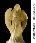 Small photo of White glass angel with wings tinged yellow in sunlight with dark background