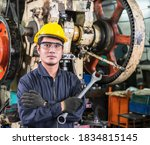 A factory worker in uniform and a yellow hard hat is standing, looking camera, and showing a wrench in his hand to ready working in the factory, and there are metalwork machines in the background. - stock photo