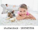 little girl lying on rug with... | Shutterstock . vector #183585506