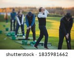 Small photo of Group of golfers practicing and training golf swing on driving range practice, men playing on golf course, golf ball at golfing complex club resort