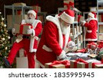 Many Busy Santa Clauses Packing ...