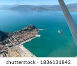 Aerial photograph of Nafplion Greece. Old city centre with castle in the harbour entrance. Gulf of Argolis and mountains under a clear sky