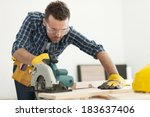 Small photo of Focus carpenter sawing wood board
