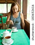 Small photo of Agitated female restaurant visitor seeing something disgusting in her cup of tea