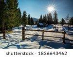 sunshine over alpine village in winter snow, Slovenia - stock photo