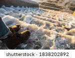 Small photo of Danger of slipping. Female boots on rough slipper ice surface. A woman in brown leather shoes descends the slippery ice ladder.