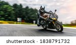 Small photo of motorbike on the road driving fast. having fun on the empty highway on a motorcycle journey. copyspace for your individual text. Fast Motion Blur effect