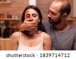 Small photo of Face of scared woman victim while man covers her mouth. Violent aggressive husband abusing injuring terrified helpless, vulnerable, afraid, beaten and panicked wife.