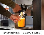 Small photo of Man fills a plastic bottle with squeezed orange juice from a juicer in supermarket. Fresh orange juice in hypermarket. Professional orange juicer machine