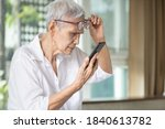 Small photo of Asian senior woman with eye glasses,try to read messages,gaze at the small text on mobile phone,age related macular degeneration,blurred vision,poor eyesight problems,eye disease of the old elderly