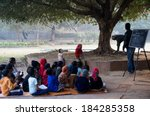Small photo of Delhi, India: 4th Jan 2014 - Poor children being taught in an open air classroom by volunteers. Classes like this (madrasa) are often held at the hauz khas village in Delhi