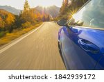 CLOSE UP, LENS FLARE: Idyllic view of sunlit Dolomites as blue sportscar drives down scenic road. Cinematic shot of golden sunbeams reflecting in the shiny door of a car cruising down mountain road. - stock photo