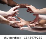 Small photo of Planet Earth. Hands of different people in touch isolated on grey studio background. Concept of relation, diversity, inclusion, community, togetherness. Weightless touching, creating one unit.