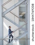 Small photo of Businessman ascending stairs in an office