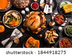 Traditional Thanksgiving day feast with delicious cooked turkey and other seasonal dishes served on black wooden table, flat lay
