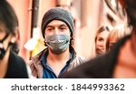 Small photo of Urban crowd of citizens walking on city street wearing face mask - New normal reality lifestyle concept with people on worried alienated mood - Selective focus on man with hat - Warm contrast filter