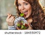 pretty woman eating fresh... | Shutterstock . vector #184550972
