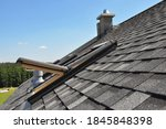 Small photo of A gray roof covered with dimensional architectural asphalt shingles with an attic skylight, ventilation pipe, air duct and chimney. A close-up on an open attic skylight.