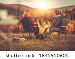 Caucasian Couple in Their 40s Seating in Front of Scenic Vista Enjoying Their Life and the Nature. Australian Silky Terrier Next to Chairs. Colorful Fall Foliage. - stock photo