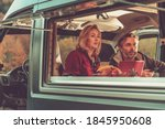 Caucasian Couple Watching Exciting TV Game Inside Self Made Camper Van RV During Scenic Autumn Weekend Getaway. Van Life Theme. - stock photo