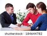Small photo of A man and a woman signing mortgage papers at advisory service
