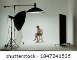 Small photo of Young barefoot man sits on chair in pose of thinker in photo studio. Male model wearing white shirt on white background among studio equipment and lighting fixtures. Backstage concept.
