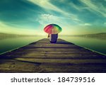 Small photo of dreamer,The man with the umbrella in colors is sitting on a fishing pier, thinks, and he's looking at the blue lake, surrounded by a hot summer's colors