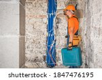 Professional Construction Contractor Worker in His 40s with Tools in His Hand Inside Concrete Blocks Built Building Interior. Construction Industry Theme.  - stock photo