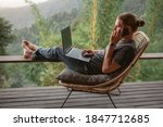 Small photo of Young man using online banking for sending money everywhere you are from laptop, sit on terrace with mounain view
