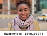 Small photo of Young attractive black woman smiling, close up portrait of urban dweller