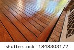 Small photo of Freshly oiled Australian spotted Gum timber outdoor covered deck with Merbau stain at Residential Home, still wet and yet to dry