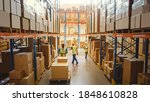 Small photo of Retail Warehouse full of Shelves with Goods in Cardboard Boxes, Workers Scan and Sort Packages, Move Inventory with Pallet Trucks and Forklifts. Product Distribution Logistics Center. Elevated Shot