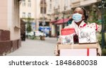 Small photo of Beautiful African American woman walking in decorated city with many christmas gift boxes after xmas shopping. Portrait of joyful grateful female in mask holds holiday presents. Surprise gifts concept