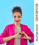 Small photo of beautiful attractive cheerful smiling young woman (mixed rase) holding her hands as heart and showing her love. Love, support, togetherness, care, diversity concept
