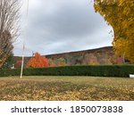 Autumn Hills of New England With Cloudy Sky, Field of Fallen Leaves, Trimmed Bushes, Old Building, Bright Orange Tree and Other Beautiful Nature