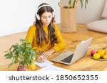 Small photo of Happy female in wireless headphones studying online course, using pc and writing in notepad, copy space. Gig economy, digital nomad, distance education. Side view of mature woman work from home