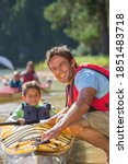 Small photo of Happy man dragging kayak in deeper water for canoeing while son is sitting in it holding the row