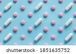 Small photo of Scattered Pills on a blue background , Medicine concept. Multiple long and round white capsue and hard pills on a blue. Colorful pattern of pills and capsules on a blue. Seamless pattern