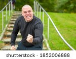 Small photo of Angry man threatening the camera with his fist as he screams abuse with a vehement expression on outdoors steps in a park