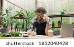 Small photo of Happy Caucasian businessman talking on cellphone while standing in apron in small floral center and writing down order details. Joyful male florist calling on smartphone at work. Own business concept