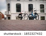 Two Parked Bicycles Stand On...