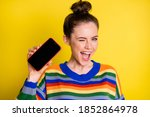 Small photo of Photo of pretty cool brunette girl show telephone blink wear rainbow sweater isolated on bright yellow color background