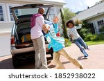 Small photo of Tilted shot of a joyous man loading luggage in back of a car as his daughter chases her brother around outdoors.
