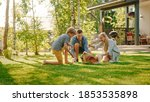 Small photo of Family of Four Having fun Playing with Cute Little Pomeranian Dog In the Backyard. Father, Mother, Son Pet Fluffy Smart Puppy, teach and train it Commands. Sunny Summer Day in Idyllic Suburban House
